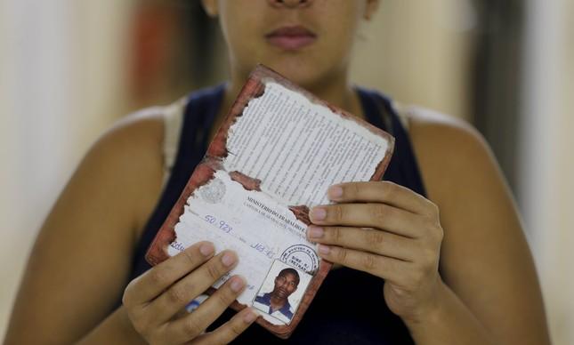 Viúva exibe a carteira de trabalho do garçom Rodrigo Serrano, morto pela PM