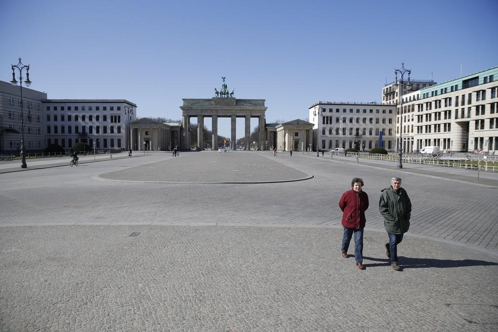 BERLIM (Alemanha) - Um casal de idosos atravessa a Pariser Platz deserta, perto do Portão de Brandenburgo, em Berlim, na Alemanha, nesta segunda-feira (23) — Foto: Odd Andersen/AFP