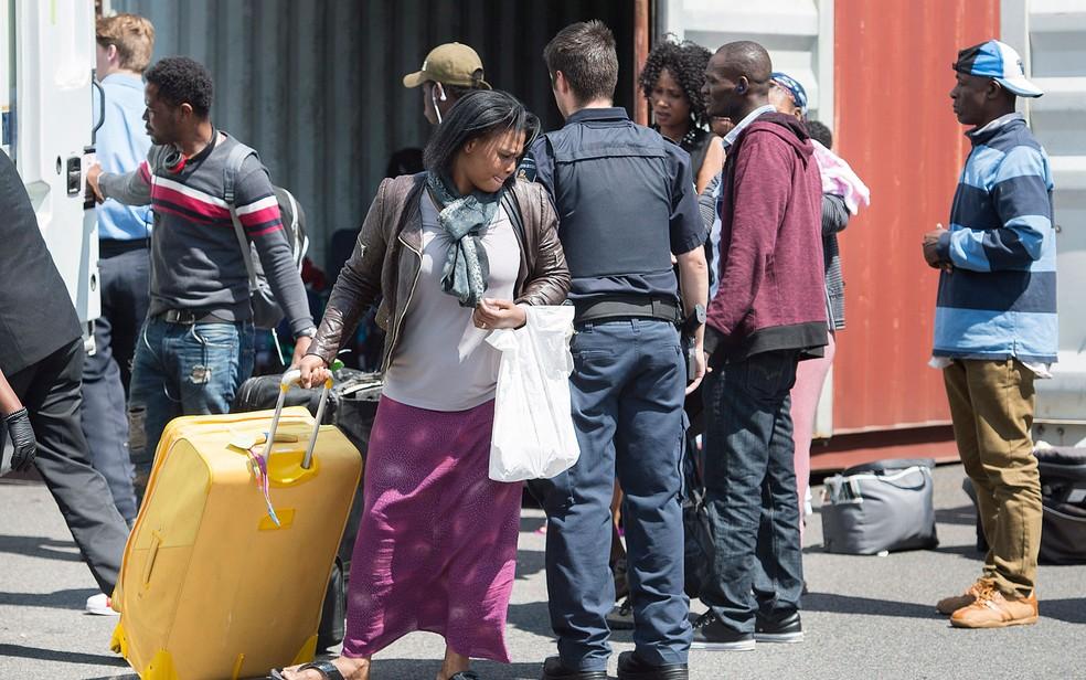 Solicitantes de asilo desembarcam de um caminhão em centro de processamento perto da fronteira entre o Canadá e os EUA em Lacolle, Quebec, na quarta (9) (Foto: Graham Hughes/The Canadian Press via AP)