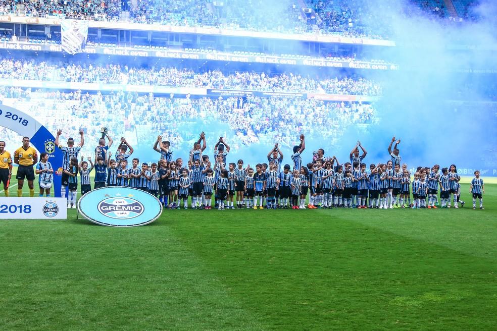 Jogadores saúdam recebimento com fumaça azul e branca na Arena — Foto: Lucas Uebel / Grêmio F.B.P.A.