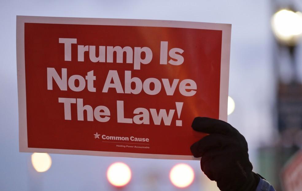 'Trump não está acima da lei', diz cartaz erguido por manifestante contra o presidente dos EUA em Cleveland, Ohio, nesta terça-feira (17) — Foto: Tony Dejak/AP Photo