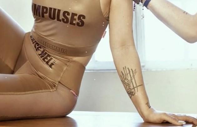 Ela mostrou, também, um símbolo tatuado no antebraço: 'Eu vi ele num livro que eu tava lendo sobre símbolos árabes (...). E significa só enriquece quem dá. E, claro, você pode interpretar isso da forma que você quiser, meu anjo' (Foto: Reprodução/ YouTube)