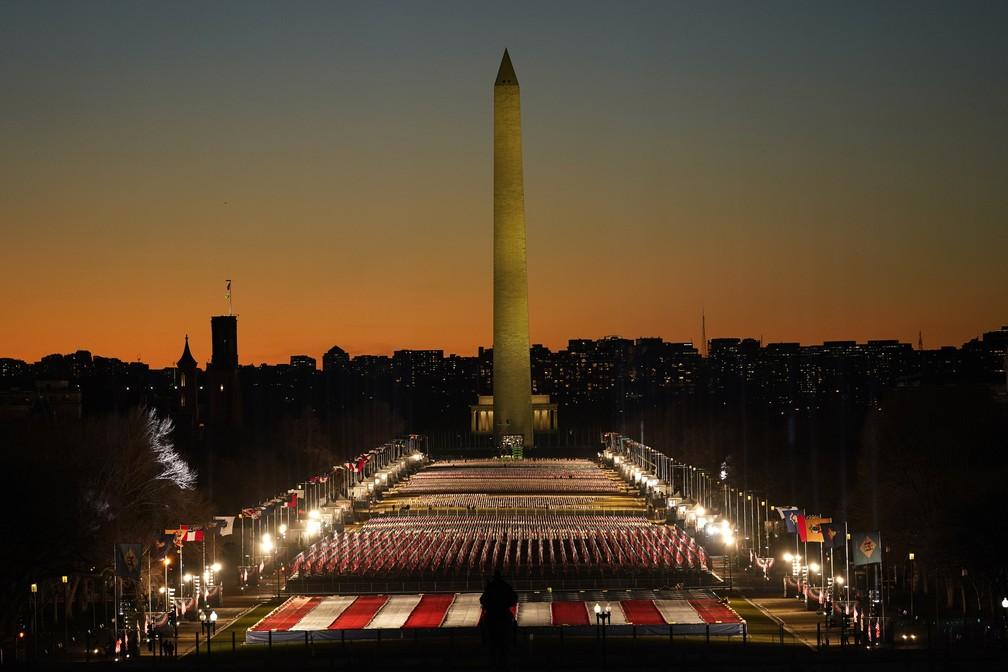 Um campo de bandeiras espalhadas pelo National Mall, com o Monumento a Washington em segundo plano, é visto durante o entardecer na noite anterior à 59ª posse presidencial em Washington, nos EUA  — Foto: Susan Walsh/AP