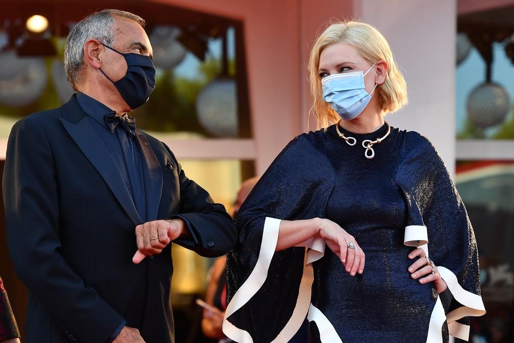 O diretor do Festival de Cinema de Veneza, Alberto Barbera, e a presidente do júri, a atriz australiana-americana Cate Blanchett, tocam o cotovelo ao chegarem para a cerimônia de abertura da mostra — Foto: TIZIANA FABI / AFP