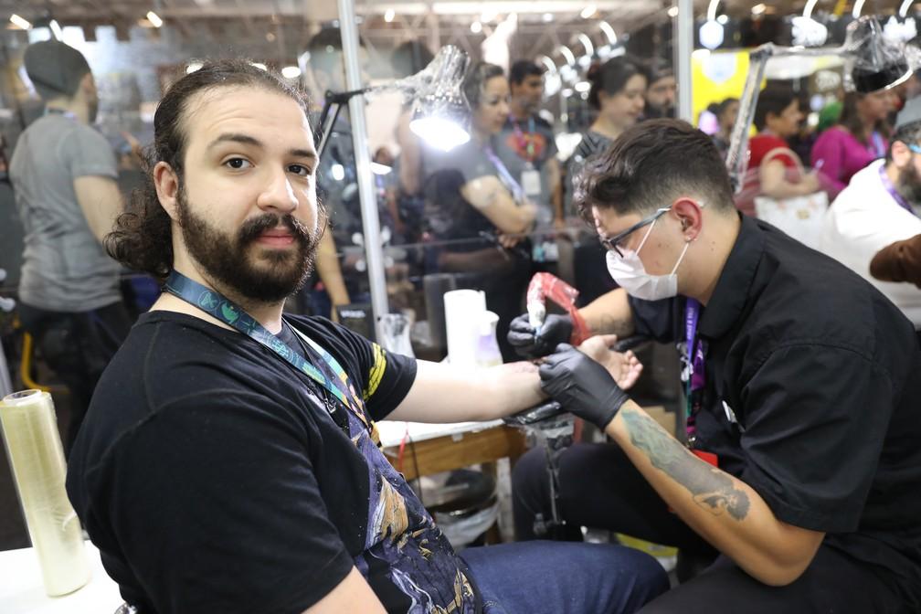 Marcos Marques tatua uma marca negra dos Comensais da Morte, de 'Harry Potter', no técnico em química Everton Batista, de 23 anos, na CCXP 2018 — Foto: Fábio Tito/G1