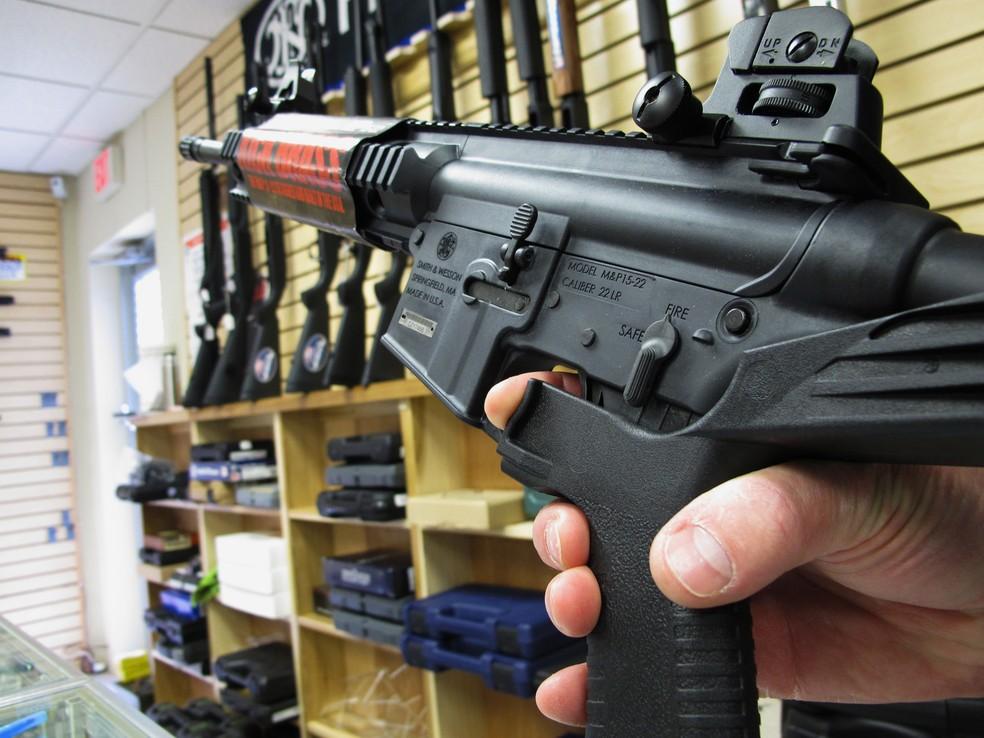 Vendedor mostra um 'bump stock' acoplado a fuzil nos EUA (Foto: AP Photo/Allen Breed)