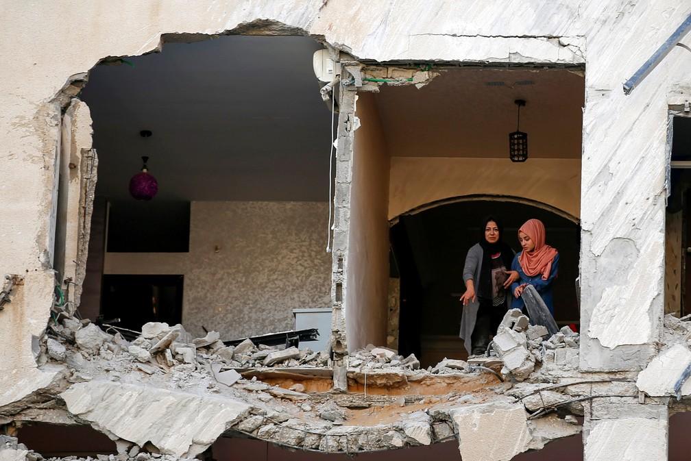 Palestinos inspecionam um prédio residencial que foi danificado em um ataque aéreo israelense na Cidade de Gaza em 12 de maio durante conflitos com Israel   — Foto: Suhaib Salem/Reuters