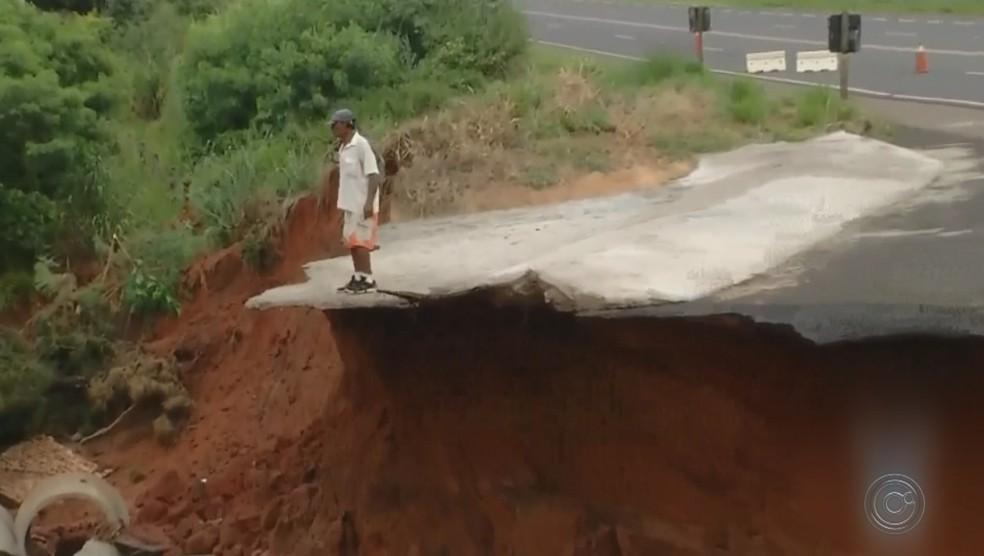 Homem se arriscou para observar a erosão que se formou nas margens da km 497 Rodovia comandante João Ribeiro de Barros — Foto: Reprodução/TV TEM