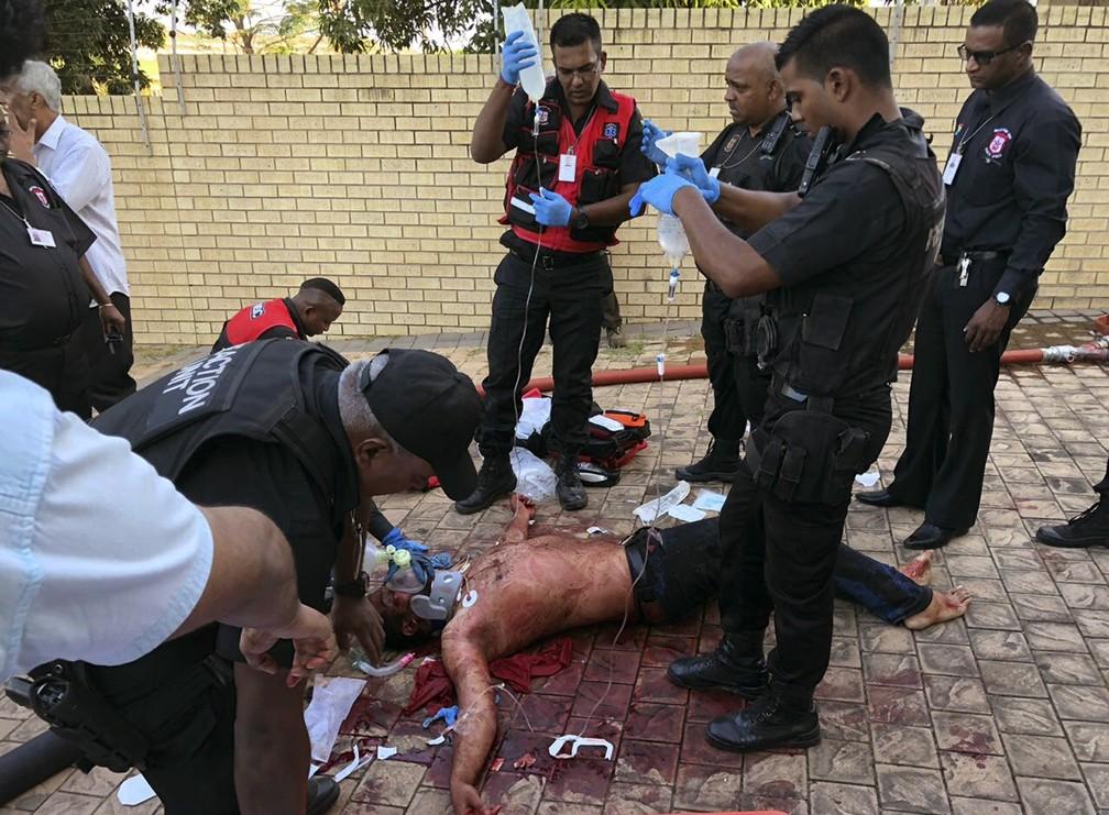 Paramédicos atendem homem ferido em ataque nesta quinta-feira (10) a mesquita em  Verulam, na África do Sul (Foto: South African Police Services via AP)