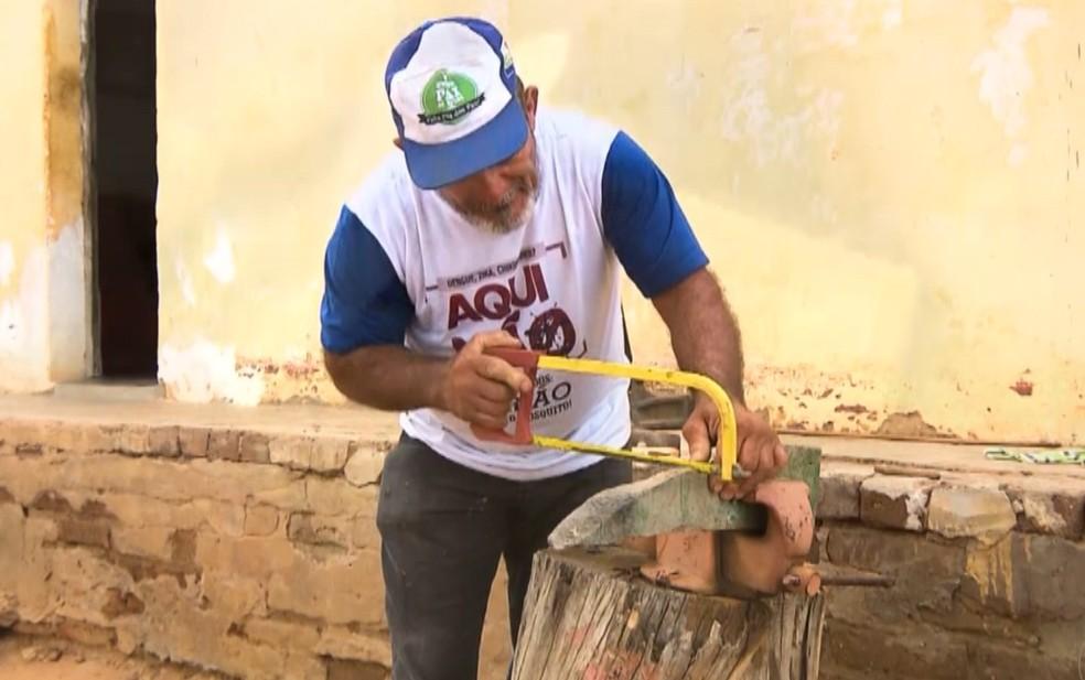 Seu Vicente manuseia máquina para esculpir miniaturas de ferramentas, no Cariri da Paraíba — Foto: Reprodução/TV Paraíba