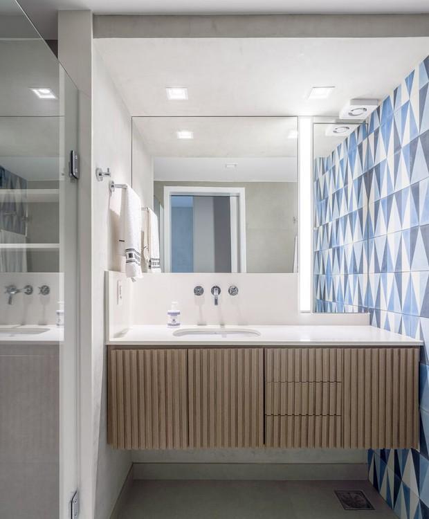 O exaustor fica estrategicamente posicionado neste banheiro assinado pelo escritório brasiliense Simmetria e quase não aparece diante do belo painel de ladrilhos hidráulicos (Foto:  Joana França/Divulgação)