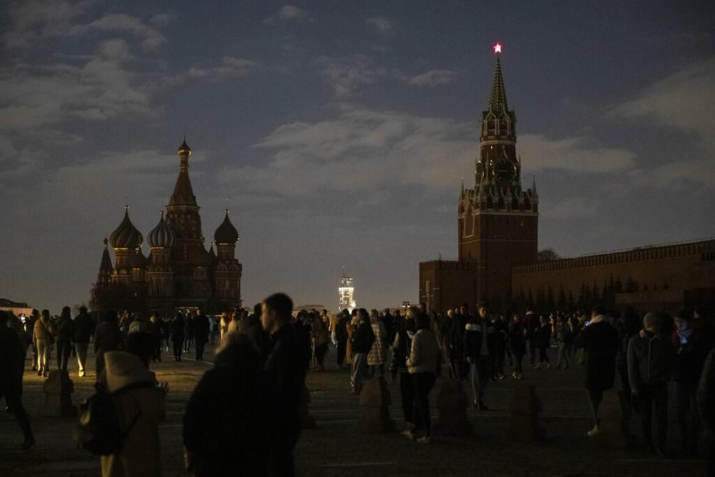 Visitantes tiram fotos na Praça Vermelha, em Moscou, das luzes apagadas do Kremlin e da Catedral de São Basílio, neste sábado (27), na Hora do Planeta 2021 — Foto: Pavel Golovkin/AP Photo
