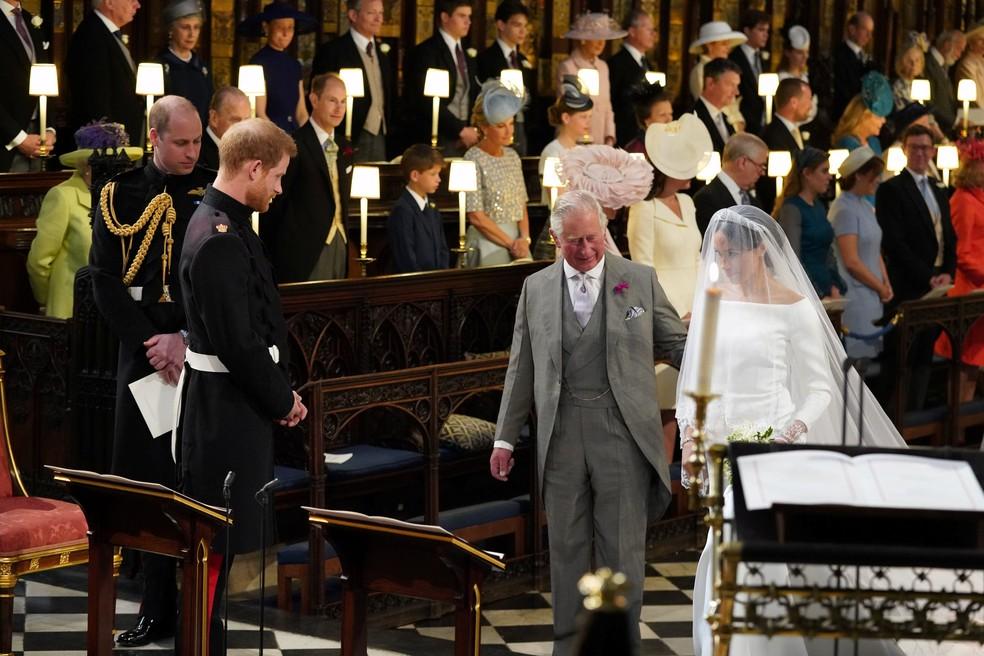 Príncipe Harry olha Meghan Markle, que entrou acompanhada pelo seu sogro, Príncipe  (Foto: Jonathan Brady/Pool via Reuters)