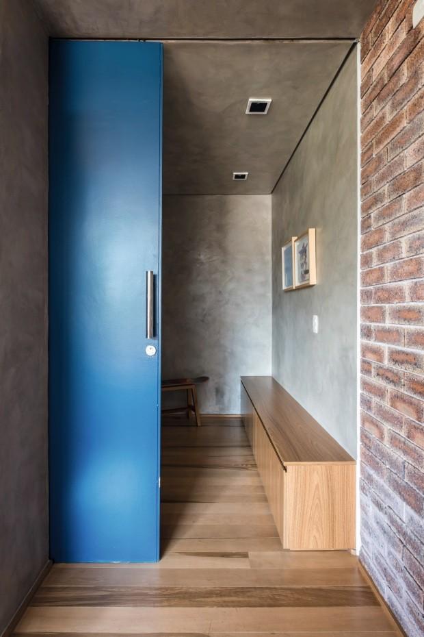 Cimento queimado e porta azul-royal criam impacto já na entrada do apartamento. O banco é uma sapateira (Foto: Nathalie Artaxo / Divulgação)