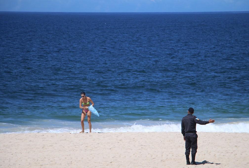 PM aborda banhista para que deixe praia. Decreto proíbe cidadãos de frequentar praias, para evitar aglomerações — Foto: José Raphael Bêrredo/G1 Rio