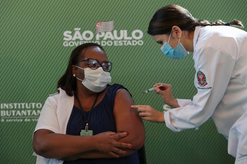 A enfermeira Monica Calazans, de 54 anos, recebe uma dose da vacina Sinovac contra a Covid-19 no Hospital das Clínicas, em São Paulo, depois que a Anvisa aprovou seu uso emergencial neste domingo (17) — Foto: Amanda Perobelli/Reuters