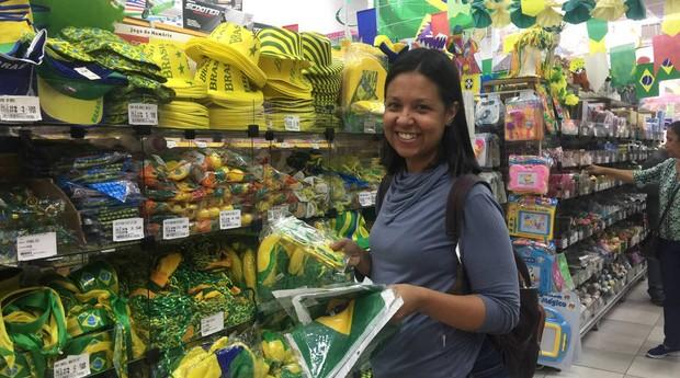 A consumidora Anelise Bueno, de 42 anos, compra produtos com tema da Copa na Saara, no Rio (Foto: Estadão Conteúdo)