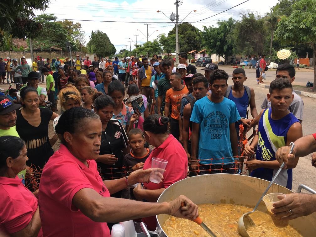 Refugiados fazem fila para receber um copo de sopa doado no 'Projeto Alimentar Encontro com o Bem' da Igreja Assembleia de Deus (Foto: Emily Costa/G1 RR)