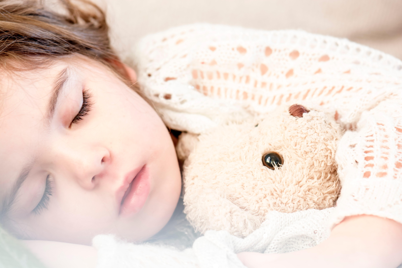 Menina dormindo e segurando um ursinho (Foto: Snapwire /Pexels)