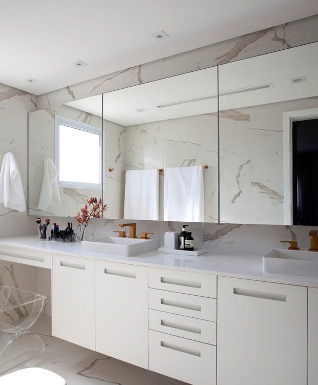 Pia dupla, metais dourados e revestimentos brancos combinam praticidade e elegância no banheiro da suíte (Foto: Marco Antônio/Divulgação)