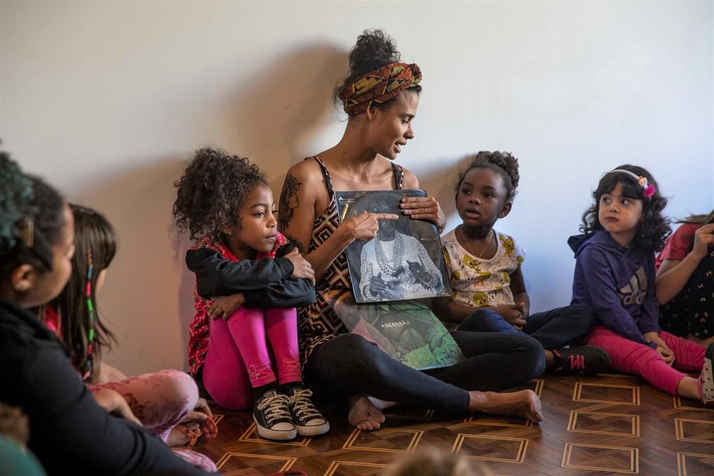 A pedagoga Juliana de Paula Costa, pesquisadora de relações étnico-raciais na Educação, realiza atividade com crianças no projeto Pisar Nesse Chão Devagarinho — Foto: Pisar Nesse Chão Devagarinho/Divulgação