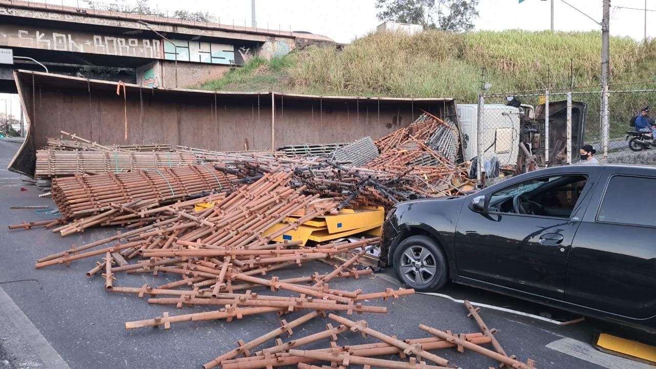 Carreta tomba e carga de ferro atinge carro em BH