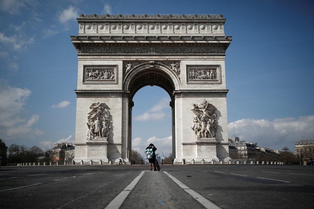 18 de março - O Arco do Triunfo, em Paris, é visto deserto após o presidente francês Emmanuel Macron anunciar que a partir do meio-dia da terça-feira (17) as pessoas poderão deixar o local onde vivem apenas para as atividades necessárias, como como comprar comida, ir trabalhar ou fazer caminhadas devido à epidemia do novo coronavírus (COVID-19) — Foto: Benoit Tessier/Reuters