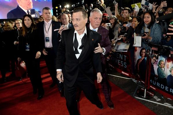 O ator Johnny Depp sendo auxiliado por seguranças em sua chegada ao red carpet de Assassinato no Expresso Oriente (2017) (Foto: Getty Images)