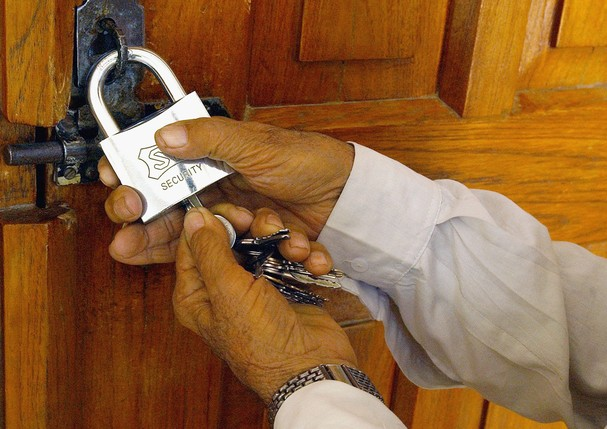 BAGHDAD, IRAQ - MAY 21: An Iraqi mosque caretaker locks the gate of al-Qazaz Sunni mosque  May 21, 2005 in Baghdad, Iraq. Sunnis clerics announced a closing of Sunni mosques across Baghdad in protest of killings of Sunni clerics that some have blamed on S (Foto: Getty Images)