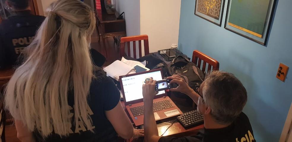 Agentes analisam computador durante 5ª fase da operação Luz na Infância — Foto: Polícia Federal/Divulgação