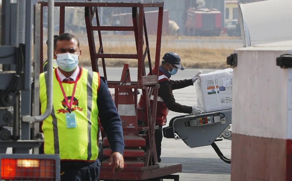 Caixa com doses da vacina de Oxford/AstraZeneca contra a Covid-19 produzidas na Índia são descarregadas no aeroporto internacional de Catmandu, no Nepal, em 21 de janeiro de 2021 — Foto: Niranjan Shrestha/AP