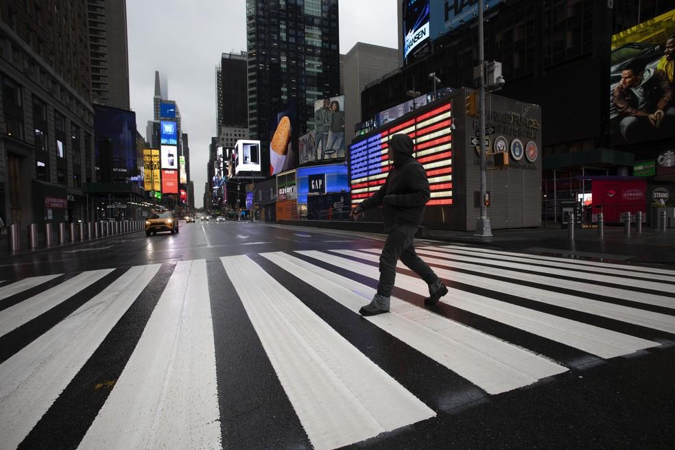 Homem atravessa rua vazia perto da Times Square, em Nova York, em meio à pandemia do novo coronavírus nos EUA — Foto: Mark Lennihan/AP