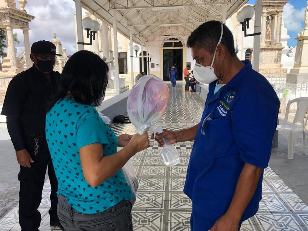 Visitantes de cemitérios em Fortaleza recebem álcool gel e são orientados a manter distanciamento social — Foto: Marina Alves/TV Verdes Mares