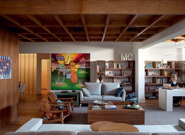 Para a sala ficar bem acolhedora, a arquiteta Fabiana Avanzi caprichou na madeira. Com home office integrado, ela recebeu assoalho de peroba e forro de pínus. O quadro dos grafiteiros Osgemeos mostra a paixão dos moradores por arte contemporânea (Foto: Lufe Gomes/Casa e Jardim)