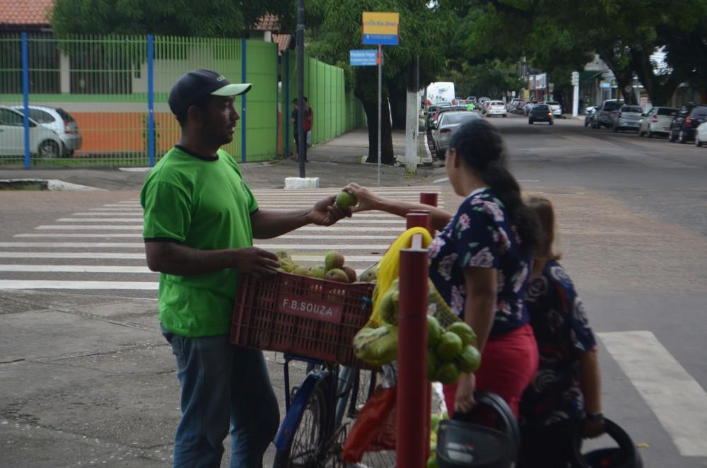 Naldo Correa oferecendo a fruta para pedestres que passavam pelo local — Foto: John Pacheco/G1
