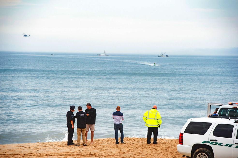 Policiais observam paria Indian Wells em Amagansett, Nova York, onde avião caiu no sábado (2)  (Foto: Gordon M. Grant/Newsday via AP)