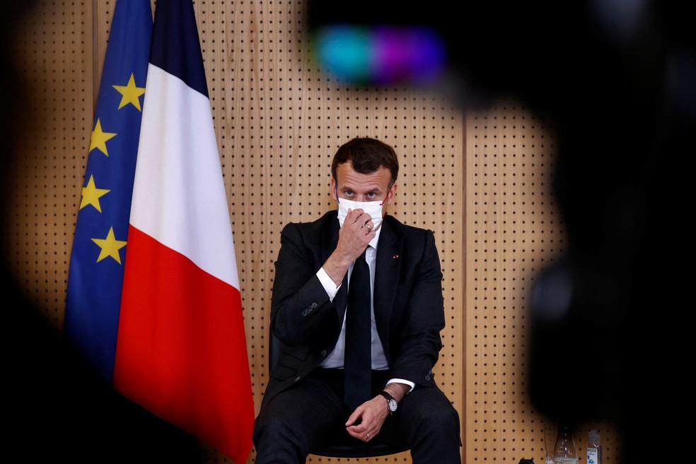 Macron ajusta a máscara ao visitar Departamento de Psiquiatria Infantil em hospital francês na quinta-feira, 14 de abril — Foto: Christian Hartmann/AFP