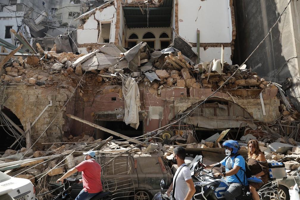 5 de agosto - Pessoas são vistas em frente a uma casa que foi destruída após enorme explosão no porto de Beirute, Líbano — Foto: Hussein Malla/AP