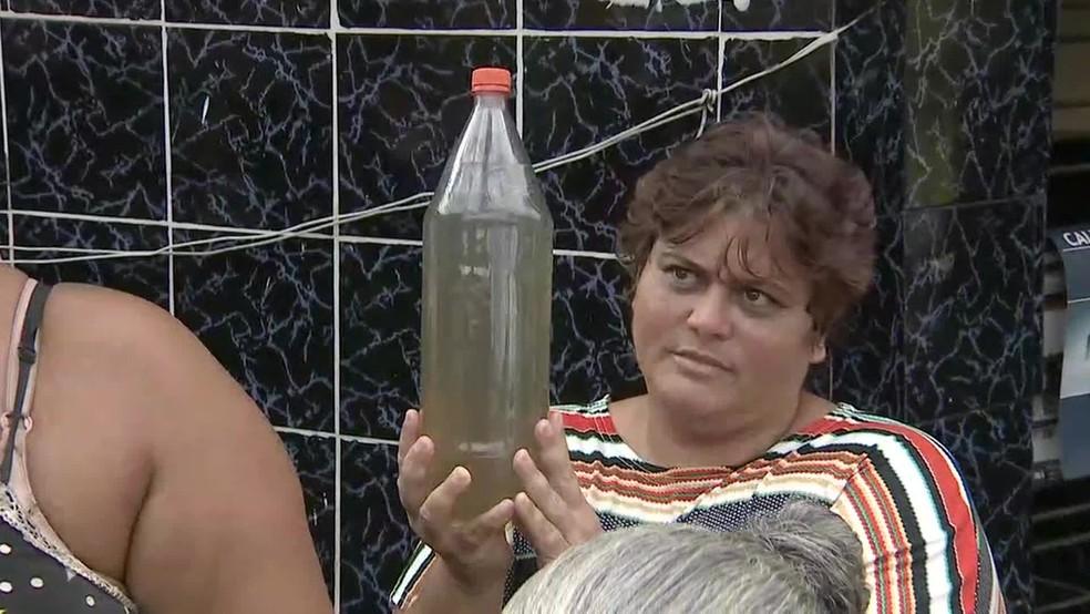 Moradora mostra água suja que sai das torneiras em São Lourenço da Mata — Foto: Reprodução/TV Globo