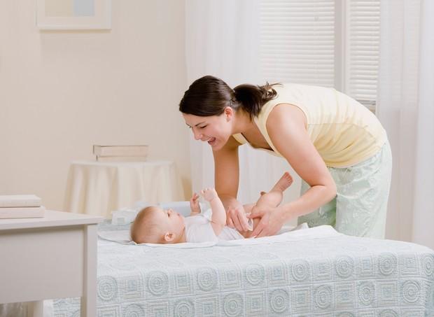 Mulher trocando a fralda do bebê no quarto (Foto: Shutterstock)