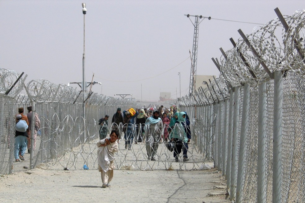 Pessoas cruzam o Portão da Amizade na cidade de Chaman, na fronteira entre Paquistão e Afeganistão, em 15 de agosto de 2021. — Foto: Saeed Ali Achakzai/Reuters