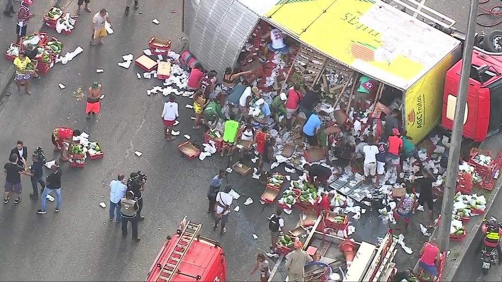 Carga foi levada por moradores da área onde o caminhão tombou, na Avenida Brasil — Foto: Reprodução/ TV Globo