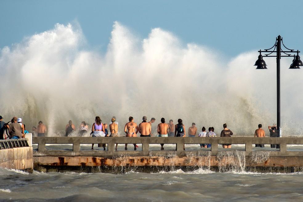 Grupo se reúne na segunda-feira (24) em píer na Flórida, nos EUA, para observar o mar revolto por causa da aproximação da tempestade Laura  — Foto:  Rob O'Neal / The Key West Citizen via AP