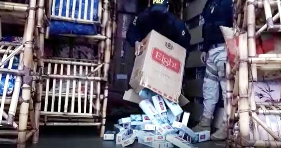 Policiais abrem uma das 450 caixas de cigarros, que totalizaram 225 mil maços — Foto: Polícia Rodoviária Federal/Divulgação
