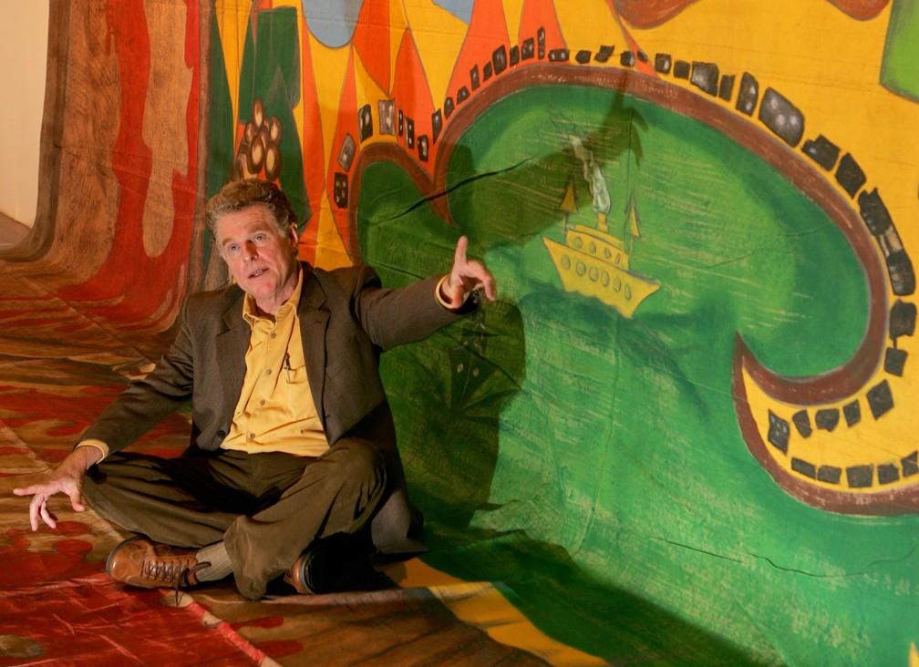 """Hélio Eichbauer em sua exposição no Centro Cultural dos Correios, no centro do Rio de Janeiro, em 2006, para comemorar seus 40 anos de carreira. Ele posa com um fundo que foi do show """"O Estrangeiro"""", de Caetano Veloso, nos anos 80, baseado no cenário que ele havia feito para a peça """"O Rei da Vela"""", nos anos 60. (Foto: Alaor Filho / Estadão Conteúdo)"""