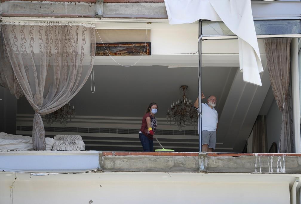 5 de agosto - Mulher limpa os destroços de seu apartamento danificado um dia após explosão atingir o porto de Beirute, Líbano — Foto: Hussein Malla/AP