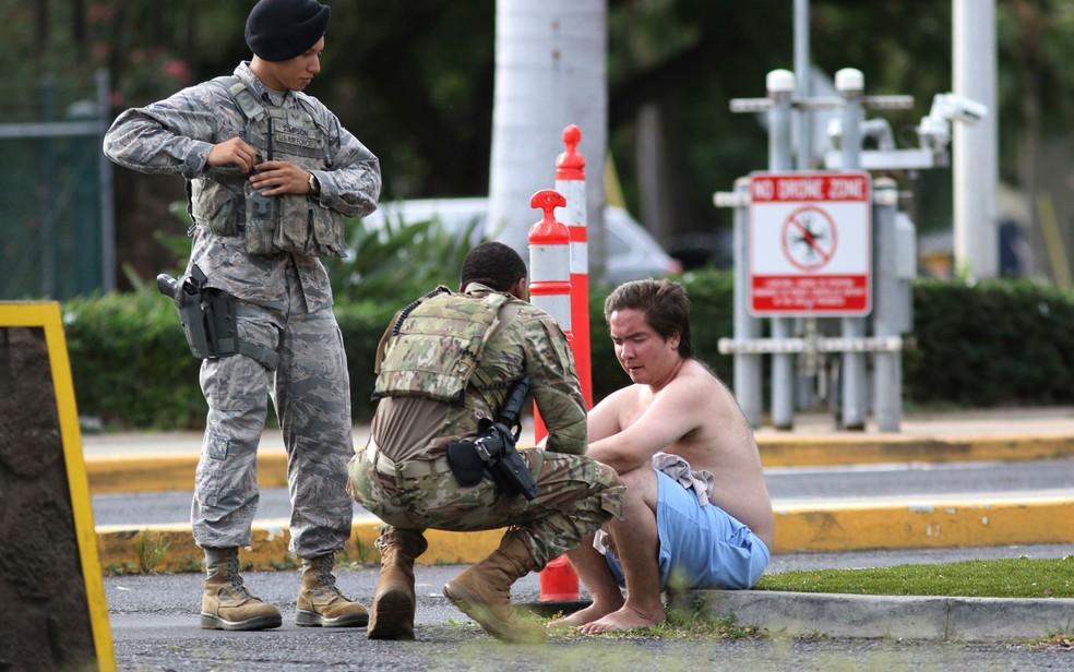 Forças de segurança atendem a um homem do lado de fora do portão principal de Pearl Harbor — Foto: Caleb Jones / AP Photo