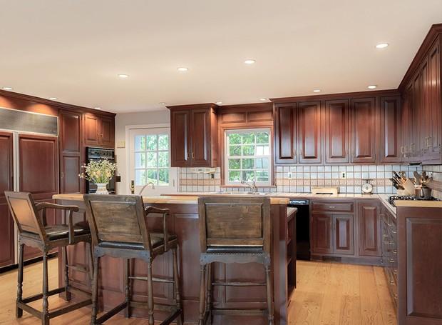 Os armários escuros da cozinha fazem com que o ambiente pareça antigo (Foto: Ellis Sotheby's International Realty/ Reprodução)