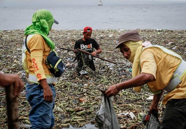 Nas Filipinas, trabalhadores retiram das águas o lixo trazido pelas enormes ondas do tufão Nida (Foto: Mark Cristino/EFE)