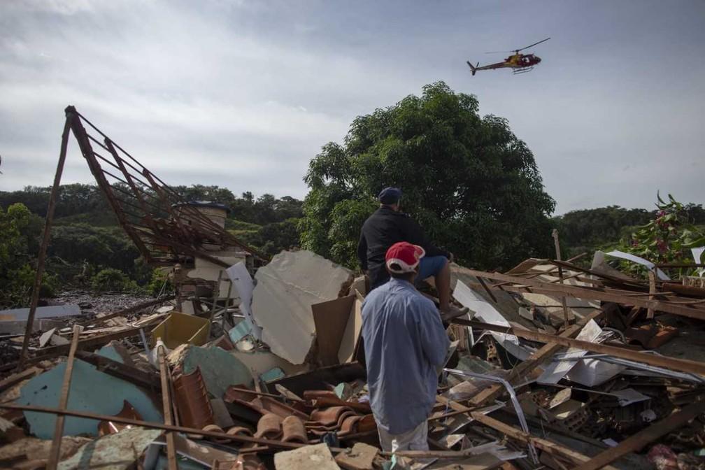 Pessoas da comunidade do Parque da Cachoeira, perto de Brumadinho, observam um helicóptero voando sobre a área atingida pela lama após o rompimento da barragem da Vale. — Foto: AFP